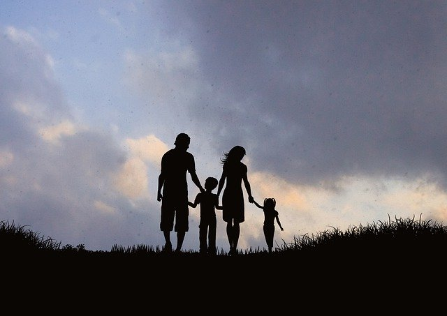 Silhouette of mother, father, and two children standing together on a grassy hill looking off into a blue sky that has a dramatic mixture of white and gray clouds.