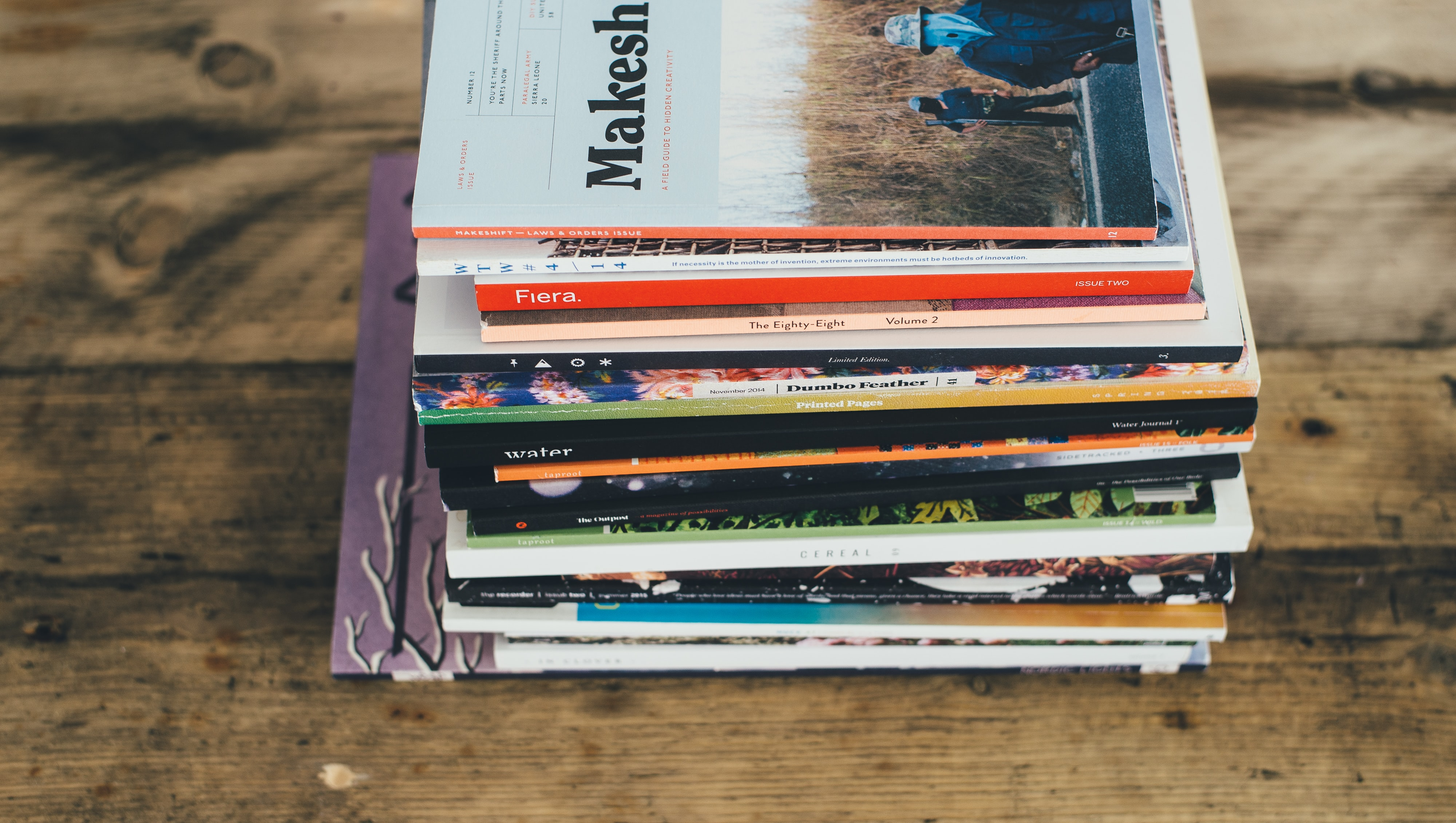 a stack of magazines on a wooden table
