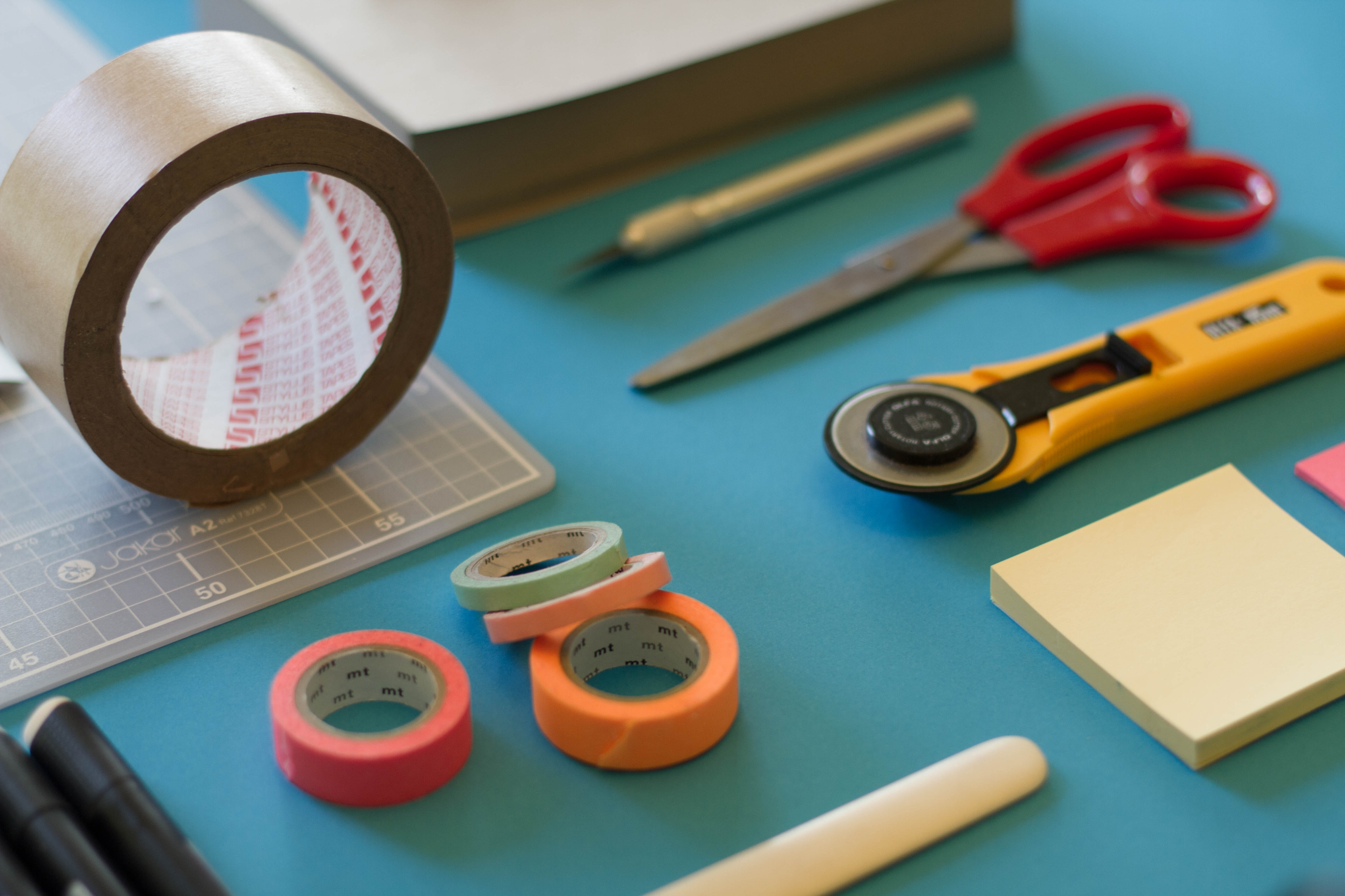 Tape and cutting tools arranged on a tabletop.