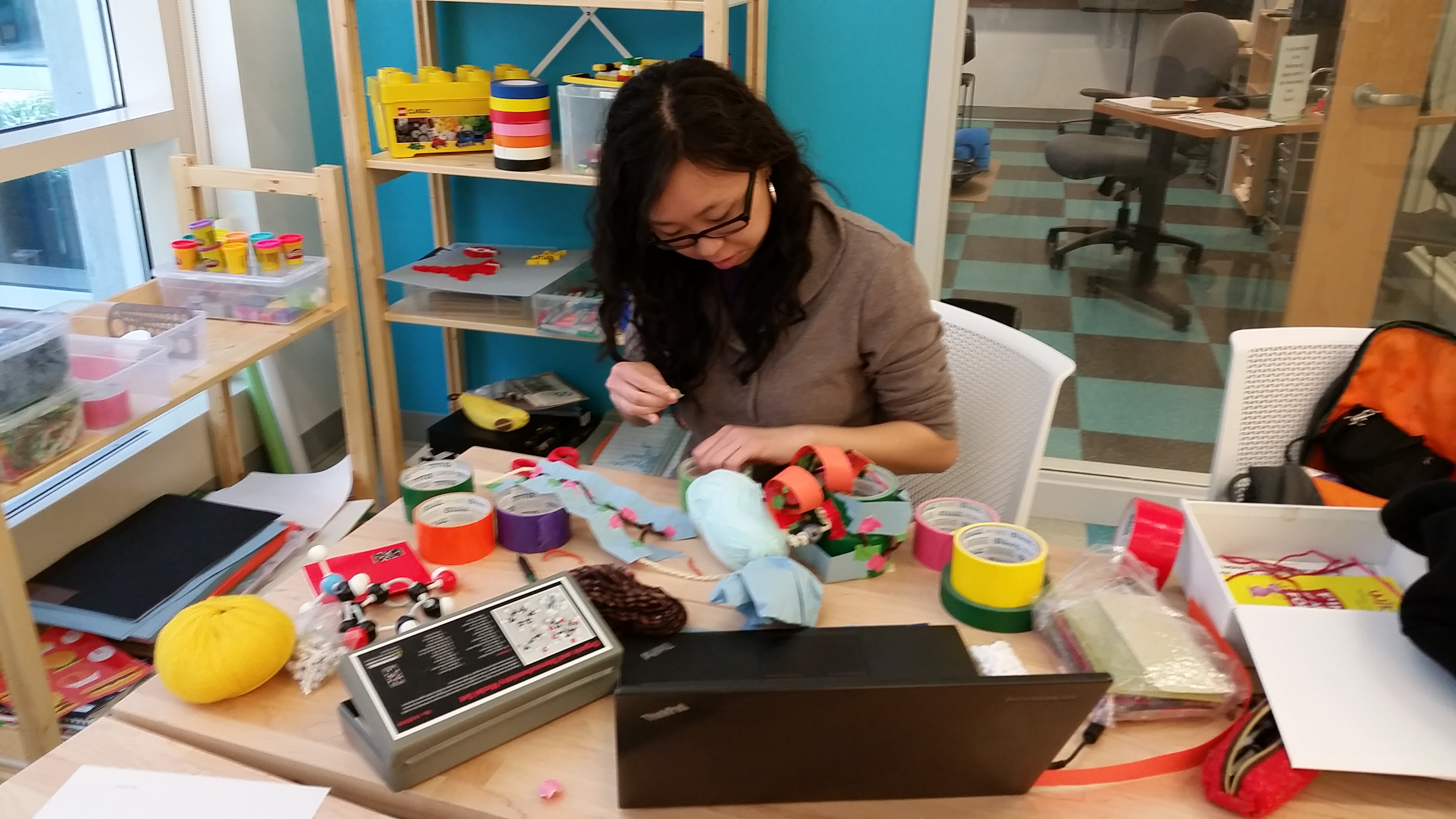 a student working on a craft project at a table