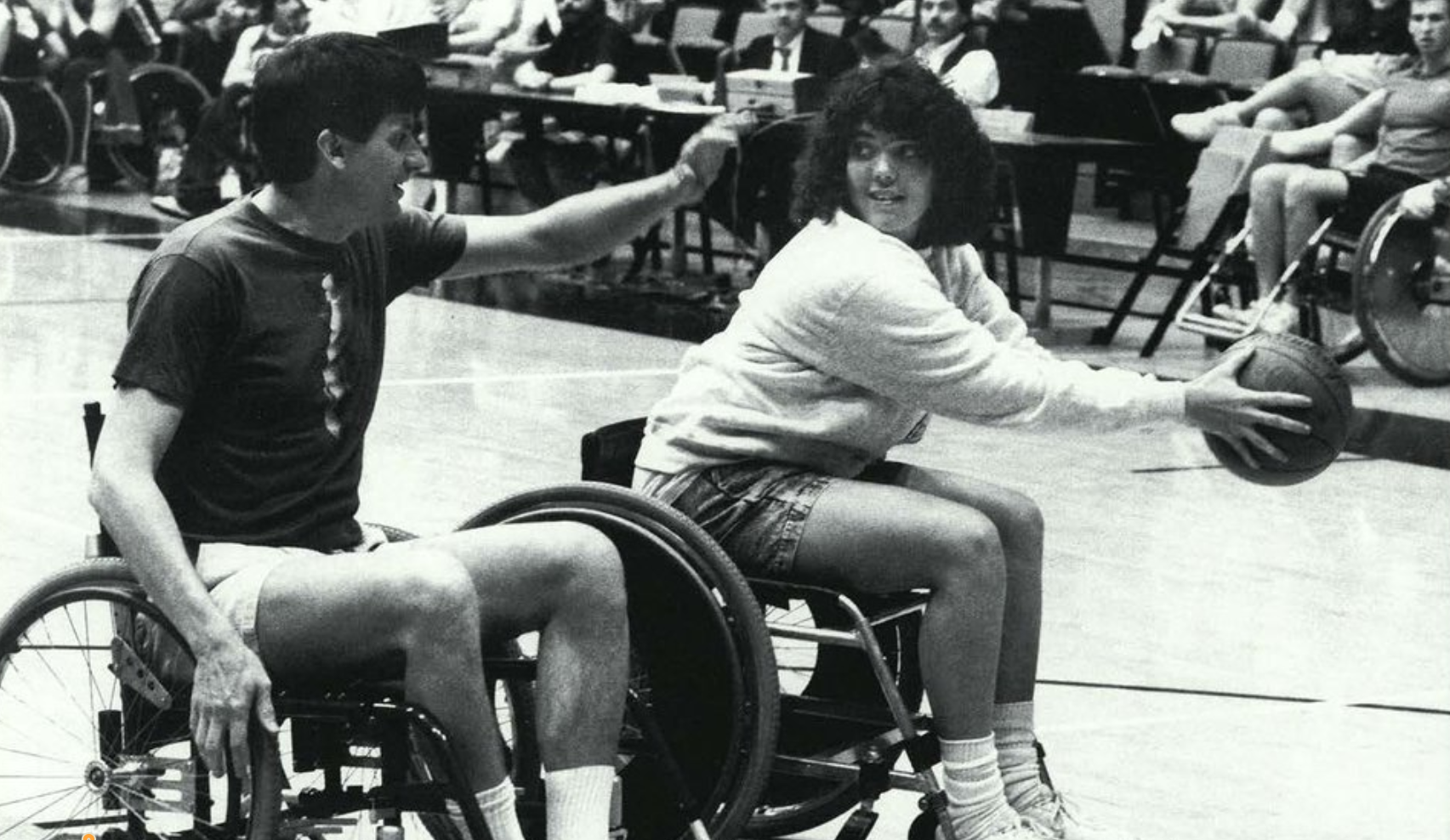 A black and white photo of two people in wheelchairs on a basketball court. One student is holding a basketball away from another student who is raising an arm as if to block her pass.