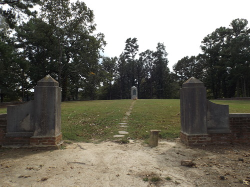 Two stone pillars frame a path leading to a stone memorial surrounded by trees.