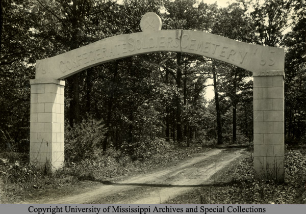 "Black and white photo of a white stone arch that reads ""'61 Confederate Soldiers Cemetery '65"""