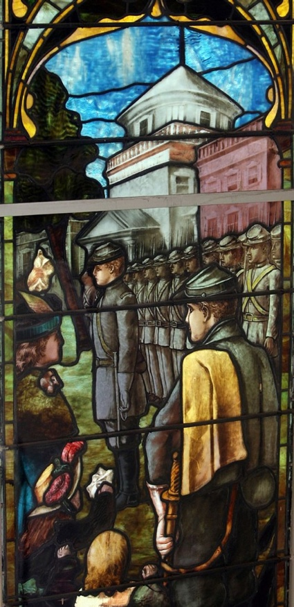 Part of a stained glass window depicting Confederate soldiers in gray uniforms in front  of a tall white building.
