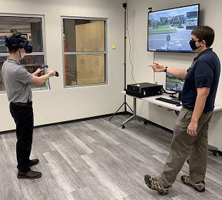 student using a standing VR station with staff helping
