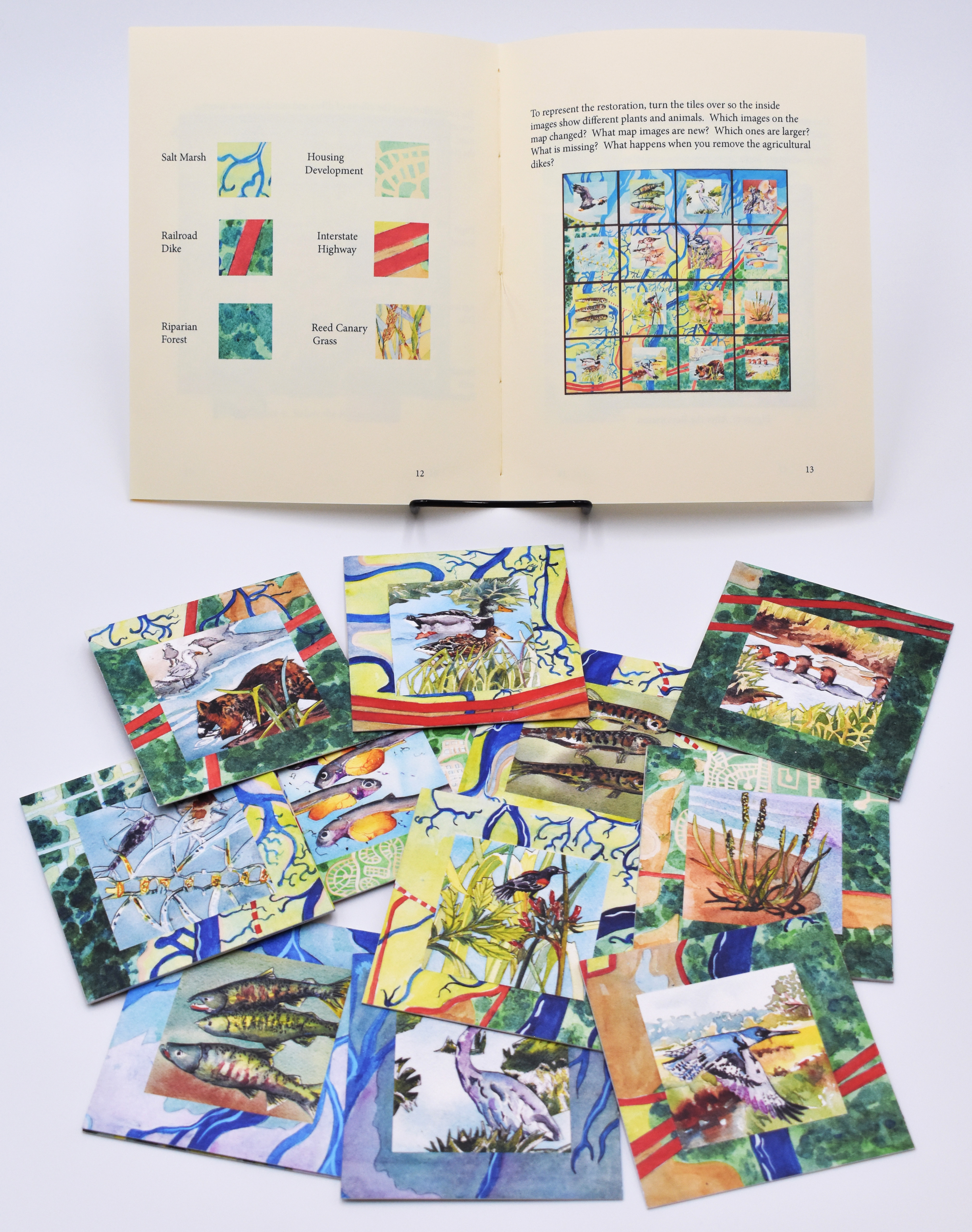 Open book behind a set of hand painted watercolor tiles