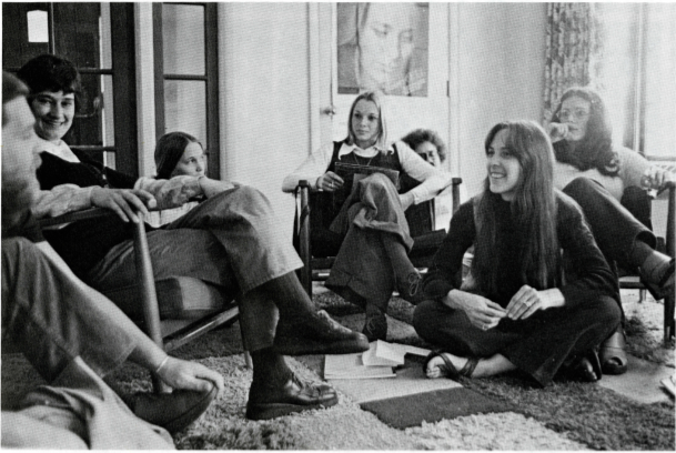 Black and white photo of women sitting in chairs and on the floor