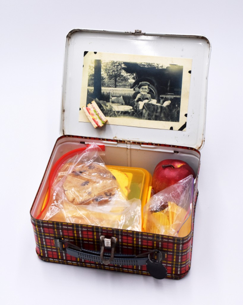 Photograph of a lunchbox with lunch box items in it, such as cookies and a sandwich and an apple.