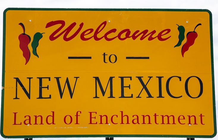 Welcome sign to the state of New Mexico decorated with red and green chile