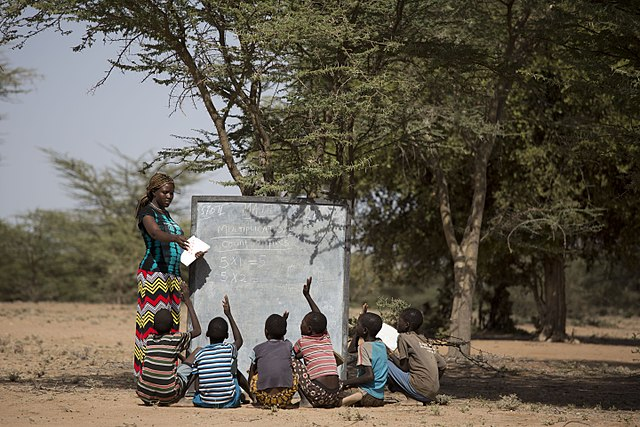 a female teacher with students teaching under a tree due to lack of facilities in malawi