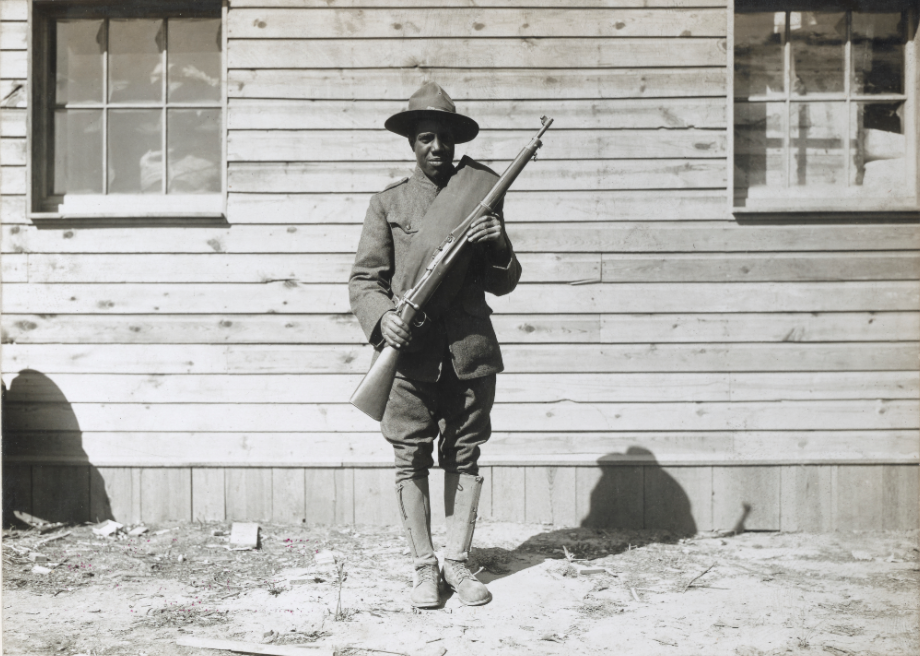 photo of African American soldier standing in front of wooden building