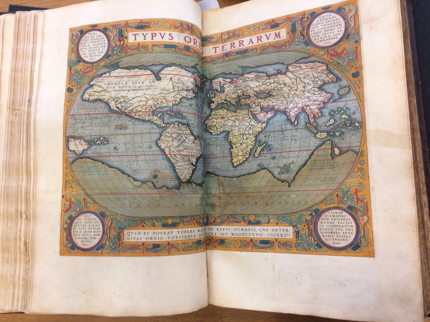 A large open book showing a hand-colored map of the world. At the top is the text Typus Orbis Terrarum.
