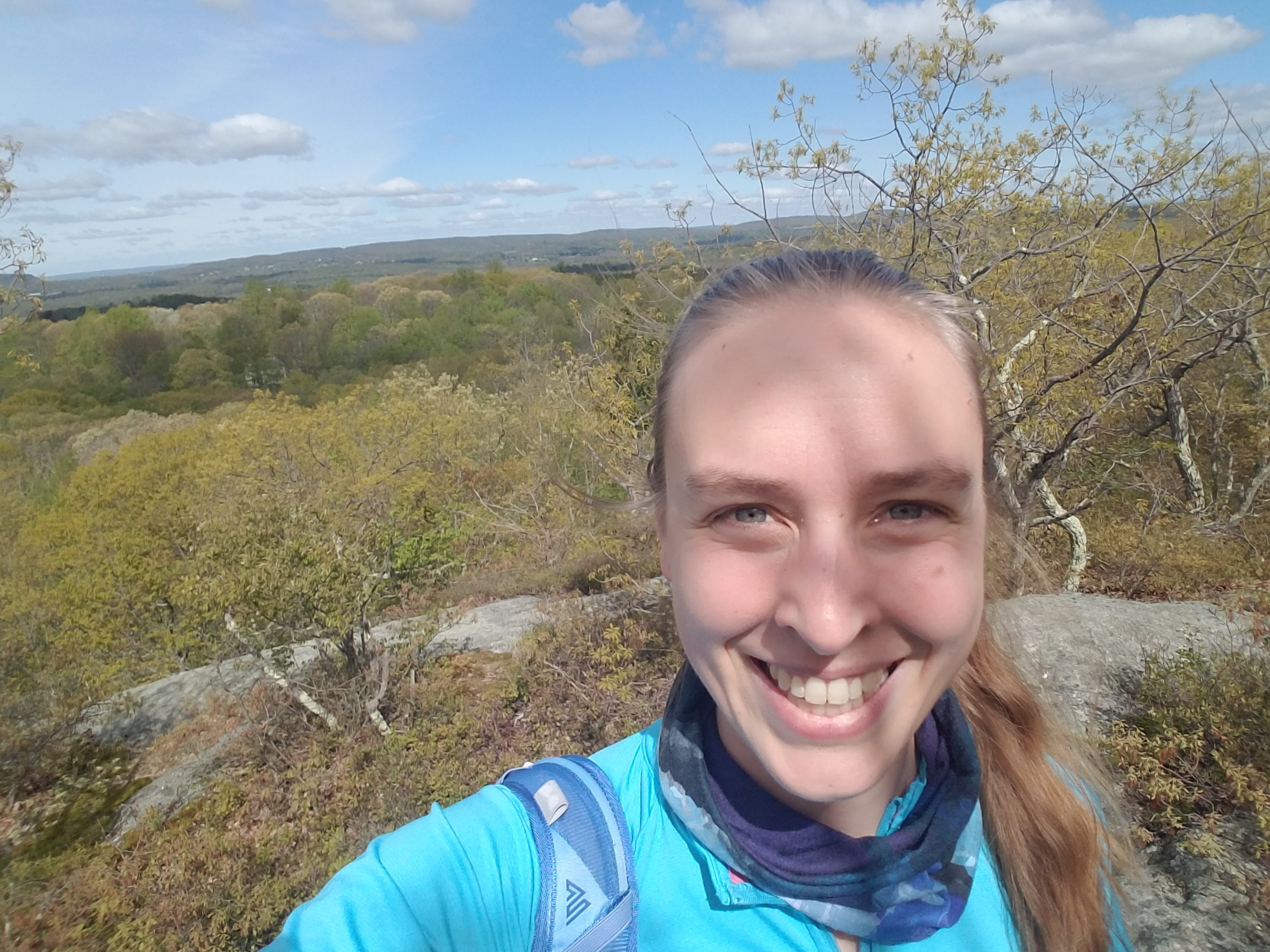 Elizabeth Peters standing on a rocky ledge overlooking a deciduous forest in early spring