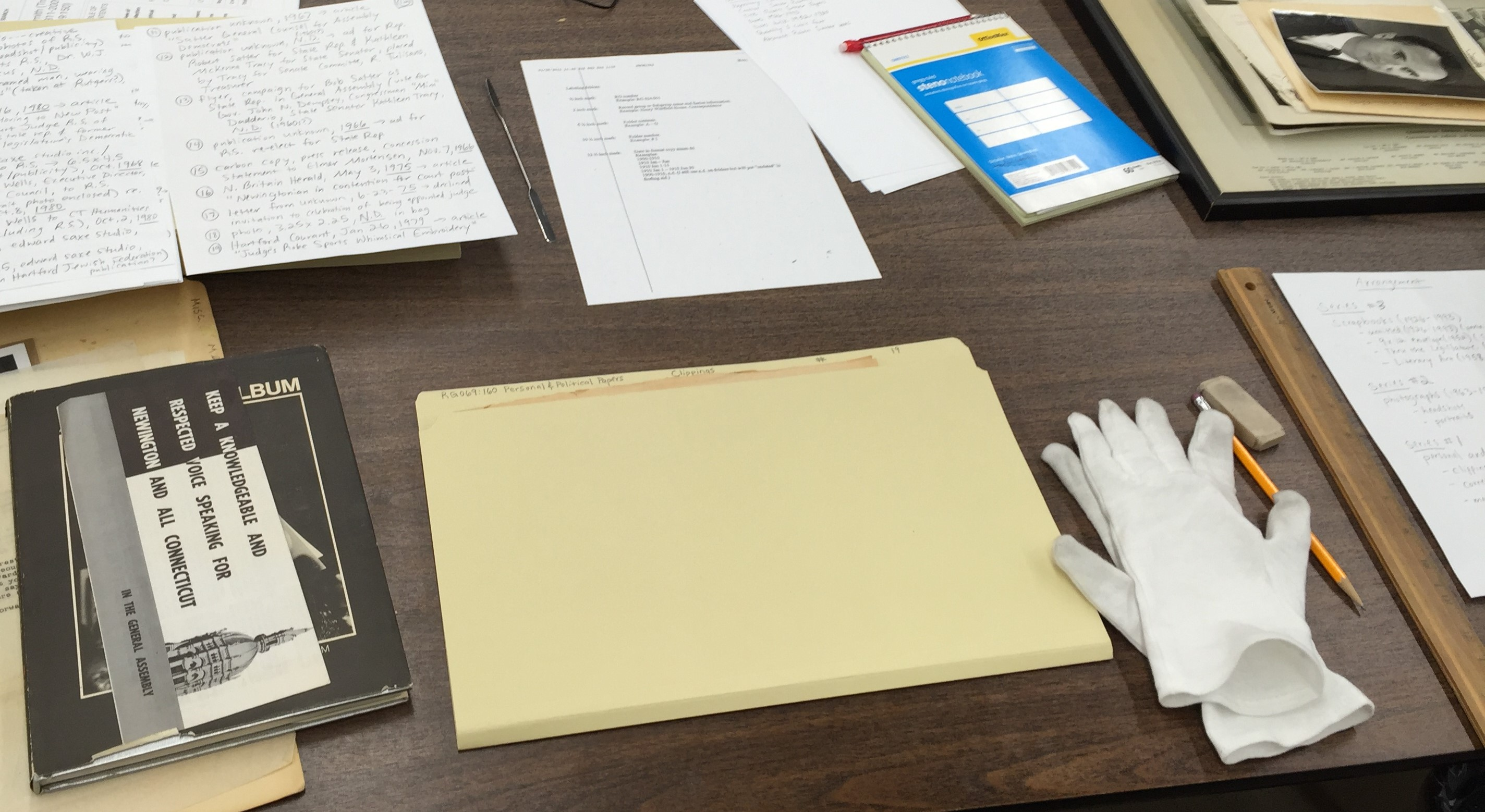 archival materials and processing tools including folders, white cotton gloves, documents, photos, and other ephemera