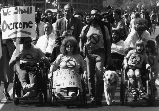 a protest for disability rights with many protestors in the foreground, some with visible physical disabilities