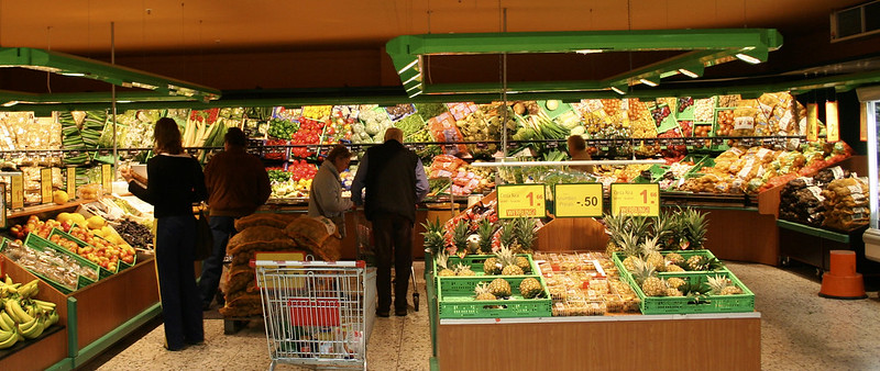 Five adults shopping in the produce section of a grocery store.