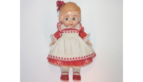 Girl doll with red and white dress and bow in her hair