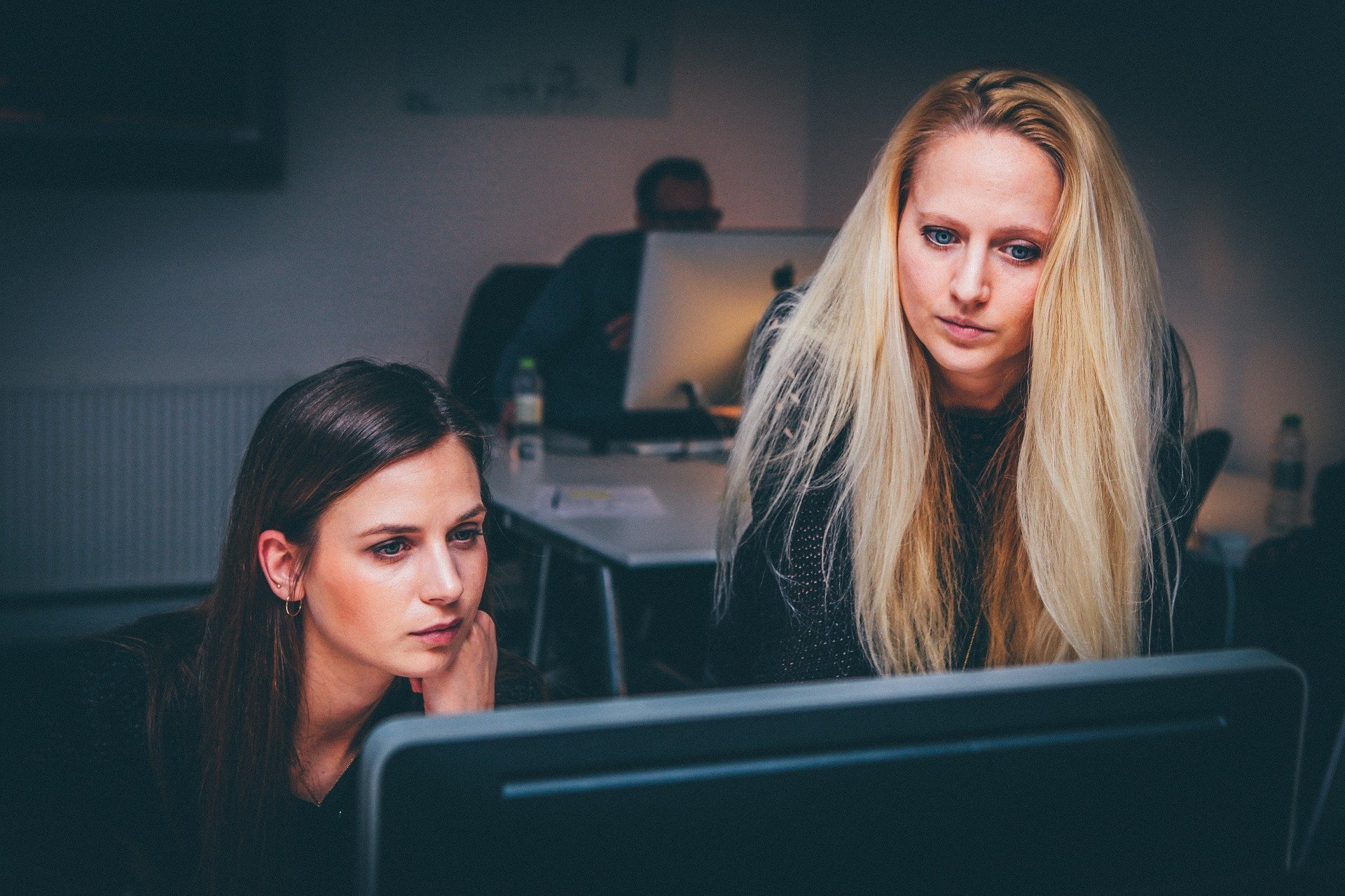 Two women working at a computer screen