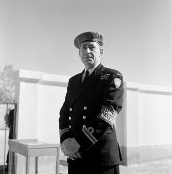 """UN Photo # 142092: Uno de los oficiales del """"Magnífico"""" vistiendo su uniforme de la marina real canadiense con una boina azul claro y un brazalete que lo identifica como miembro de la UNEF."""