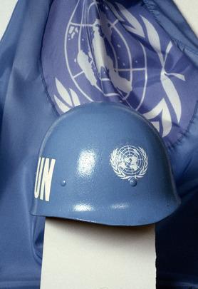 UN Photo 169095 : Casco azul y bandera de las fuerzas de paz de las Naciones Unidas