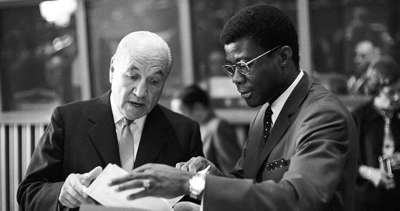 UN Photo 220585: Discussing a document are Raul Prebisch (left), Secretary-General of the UN Conference on Trade and Development (UNCTAD), and Jean-Baptiste Beieoken of the Federal Republic of Cameroon. 23 May 1966
