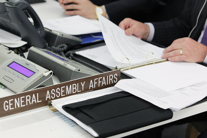 UN Photo # 585393, showing a close-up of the conference table as an official of the General Assembly and Economic and Social Council (ECOSOC) Affairs Division follows a meeting of the Fifth Committee in 2014.