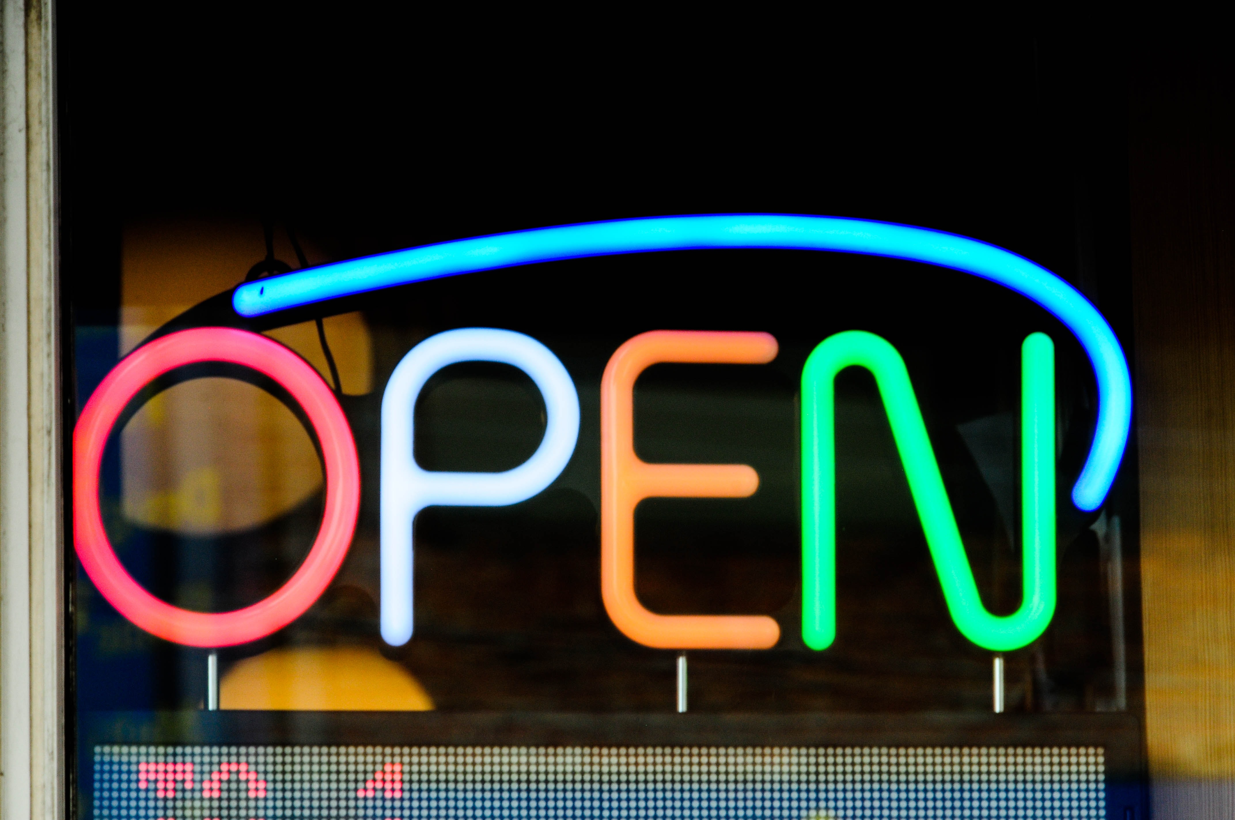 An image of an open sign in rainbow colors