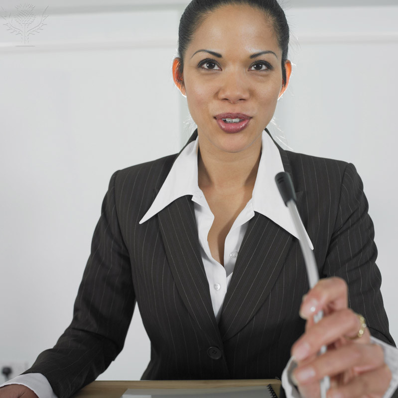 Business woman presenting into microphone
