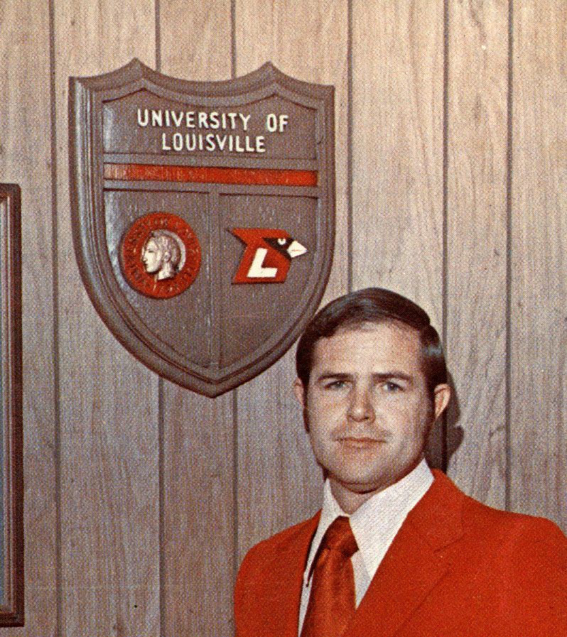 Denny Crum standing in front of plaque featuring University of Louisville's symbol, Minerva, and the athletics logo