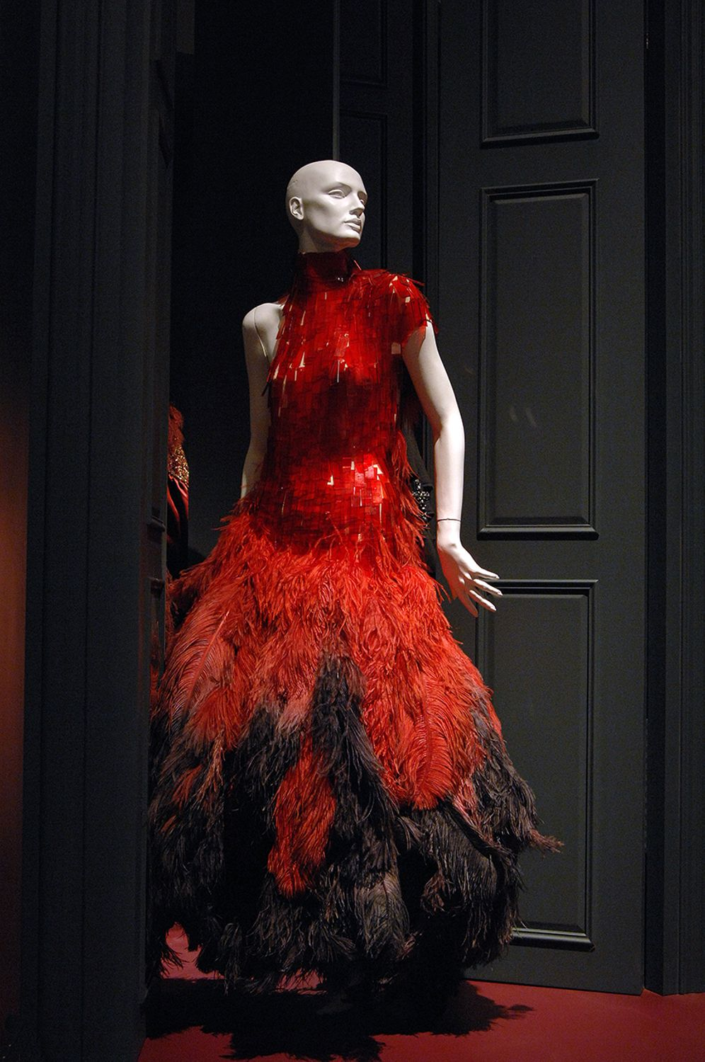 Alexander McQueen dark red glamour dress with a fitted red bodice and a black and red feathered skirt.