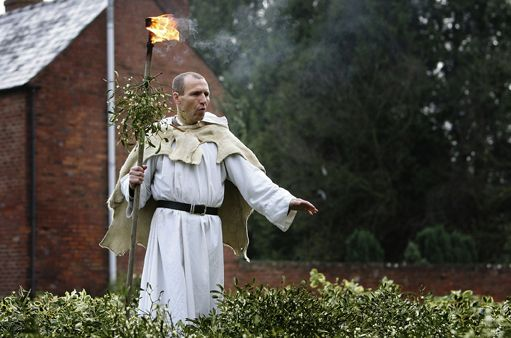 A older male druid in white robe holding incense blessing a crop of mistletoe.