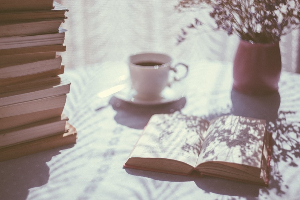 image shows a stack of books, a vase of lavender springs, an open book, and a cup of tea