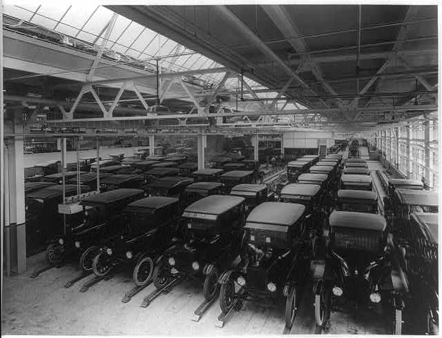Photograph shows a fleet of Ford motorcars in rows ready for delivery inside plant.