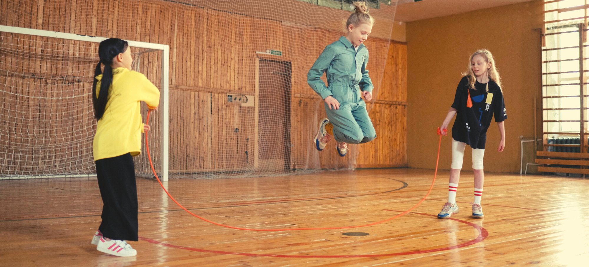 Three girls in a gym playing jump rope.