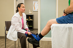 physical therapist helping patient with foot injury