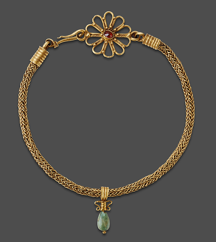 A choker-length necklace comprised of a braided gold chain with a single emerald pendant. The flower shaped closure is adorned with a garnet.