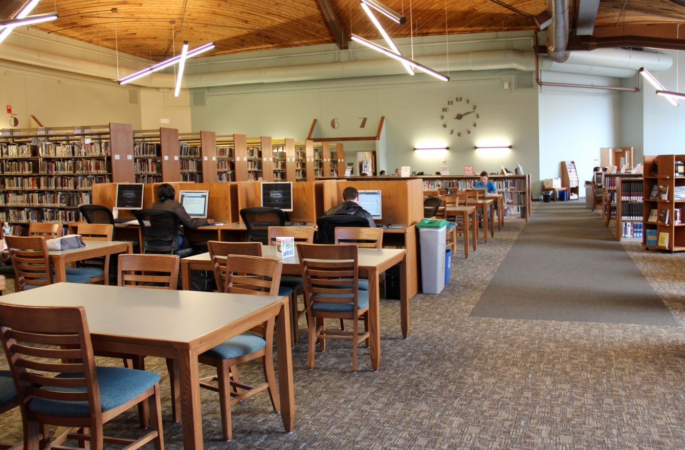 photo of the interior of the Bedford Campus library, showing computer work stations and book stacks
