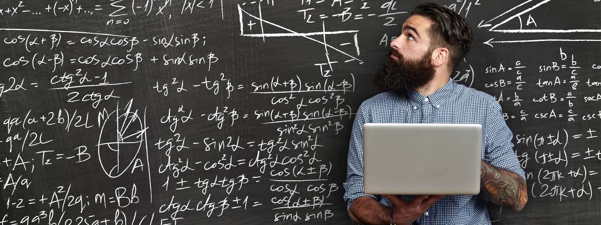 Man looking at blackboard full of equations