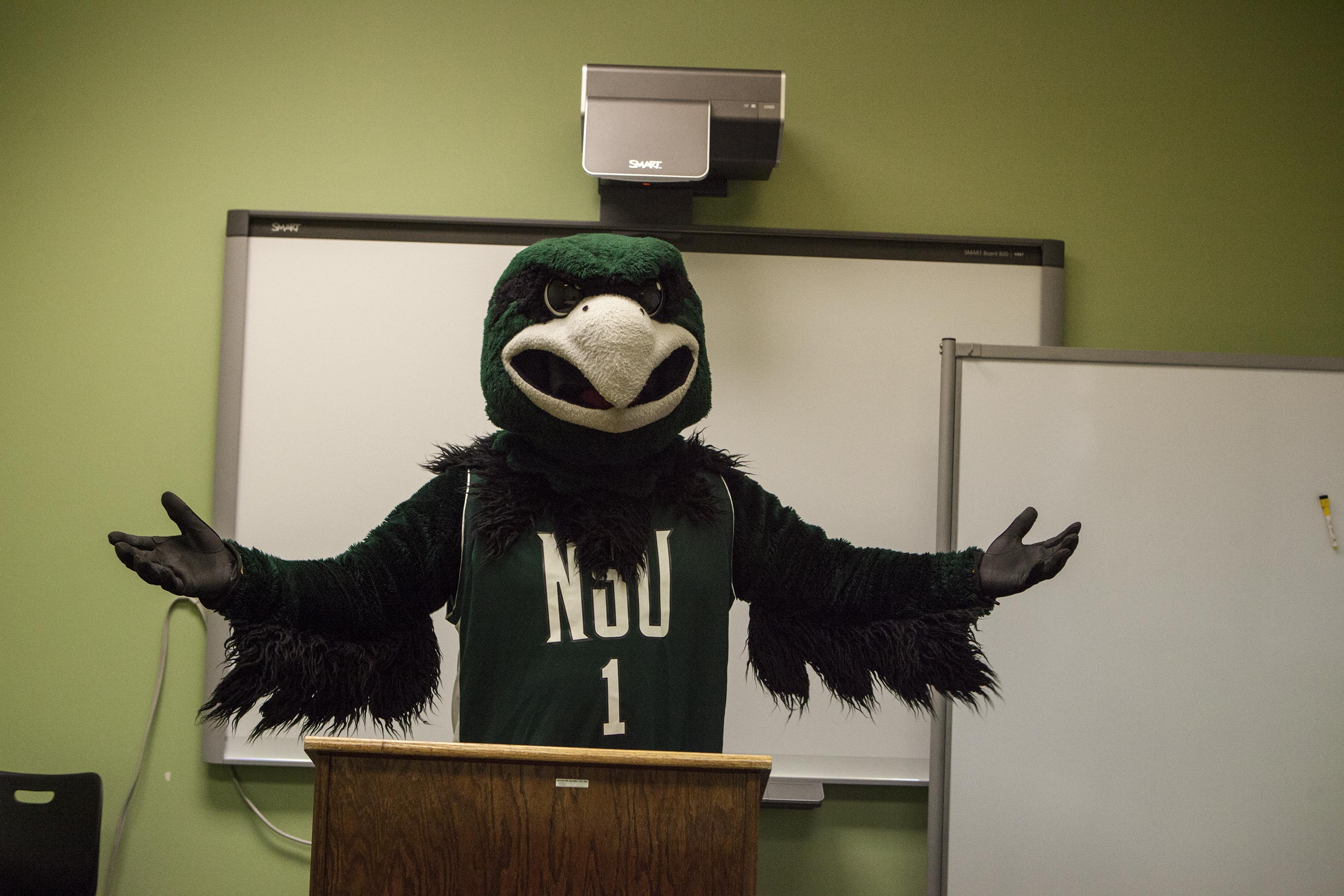 Photo of Rowdy the RiverHawk standing at a lectern in front of a SmartBoard.
