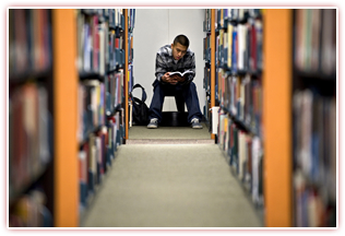Student in library. Couresy of UCI Communications.
