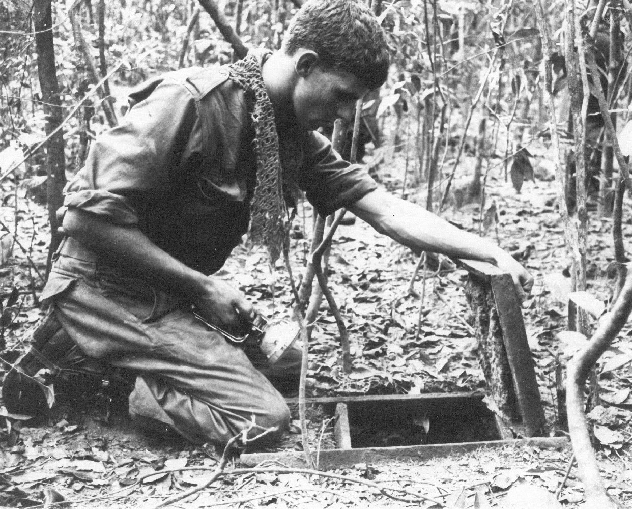 Australian soldier looking into a Viet Cong tunnel