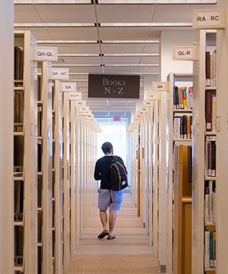student walking down row of book shelves