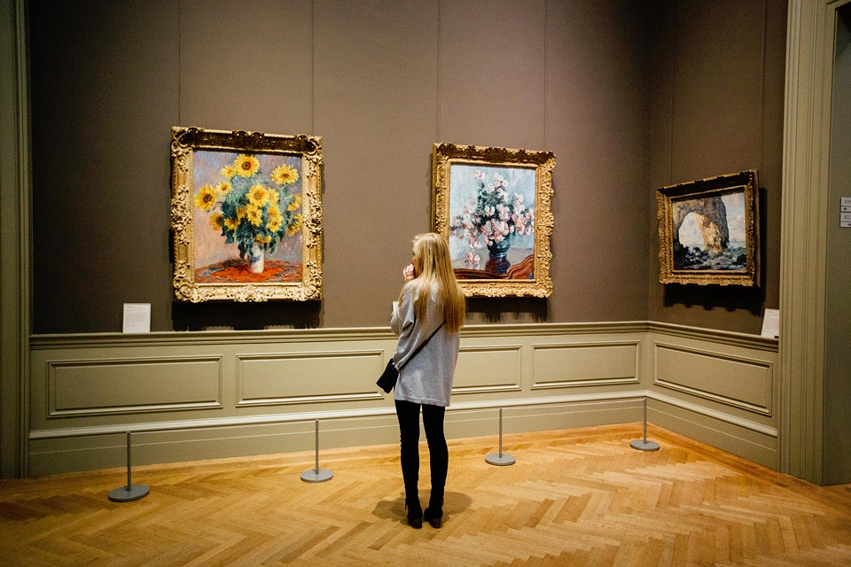 a person looking at paintings on the wall of a museum