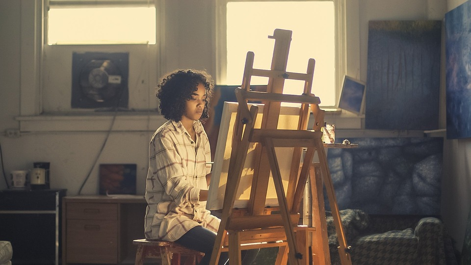 a person painting at an art easel