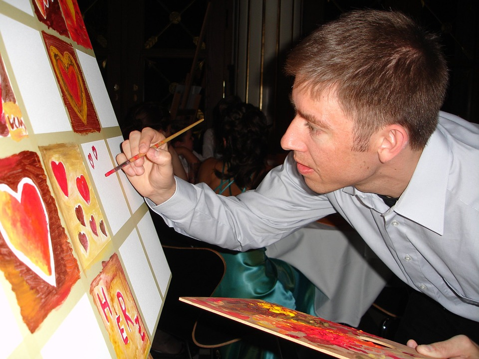 A male artist painting a grid or red hearts on a canvas