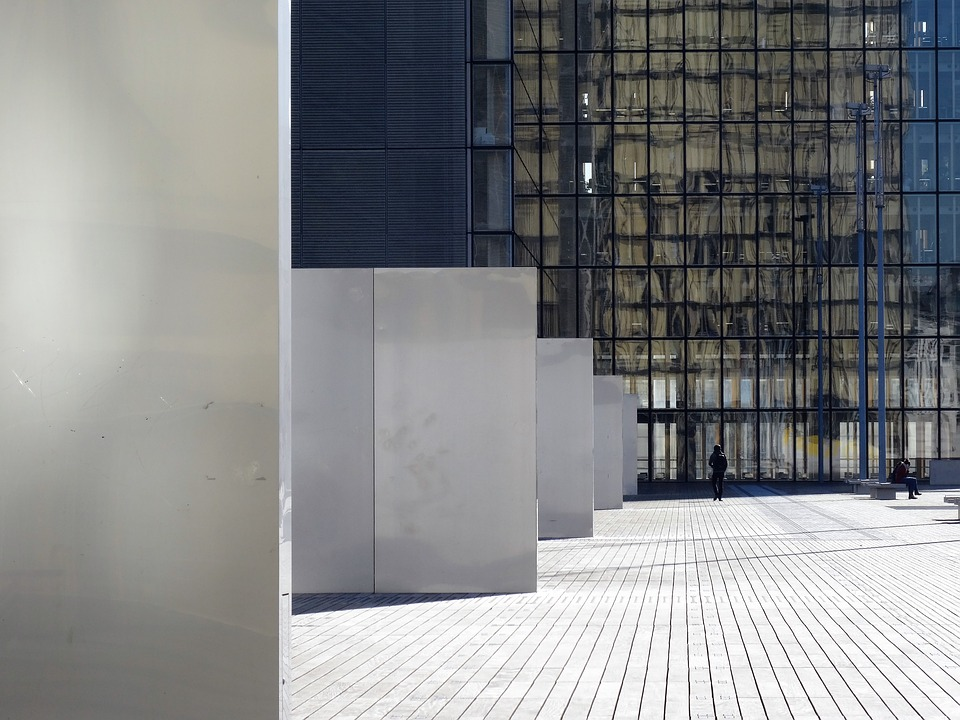 An exterior view of the  French national library (Bibliothèque nationale).  Shows a person walking in front of giant glass windows.