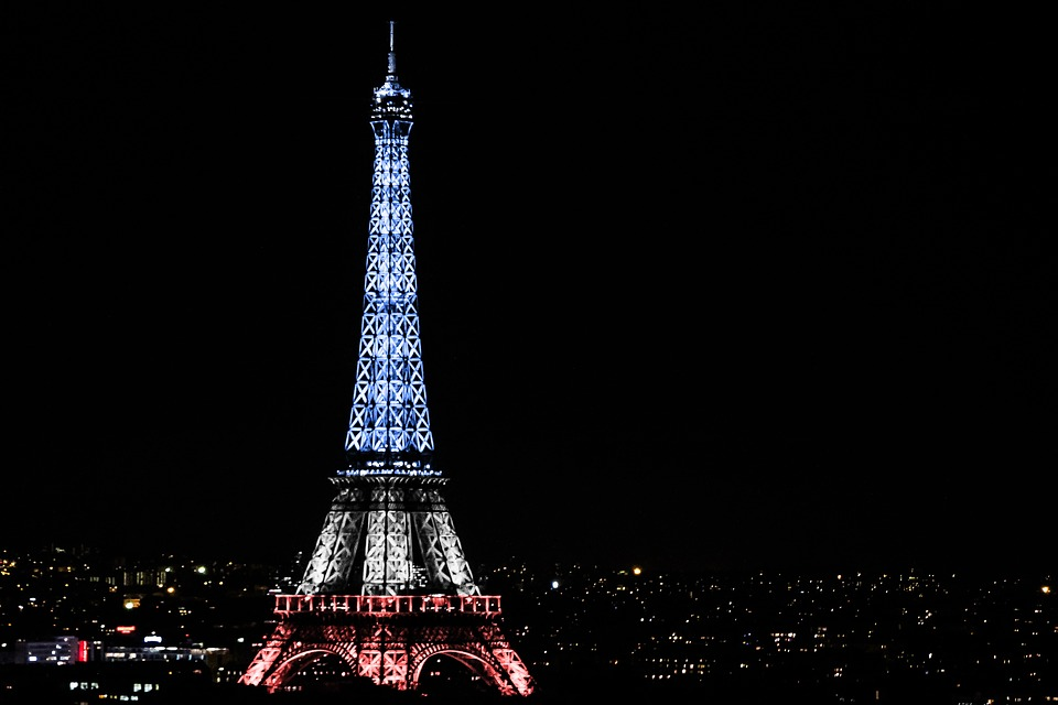 A night view of the Eiffel Tower.  Lights shine on the Tower in the French national colors--red, white, blue.