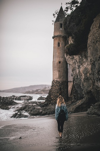 A modern woman gazes at a medieval castle on a beach.  Photo by Roberto Nickson (@g) on Unsplash