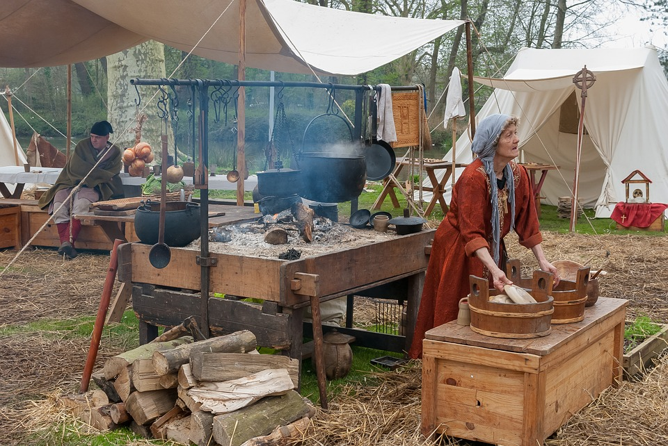 A picture of a medieval reenactment.  A man and a woman in medieval wardrobes.  The woman is crafting something.