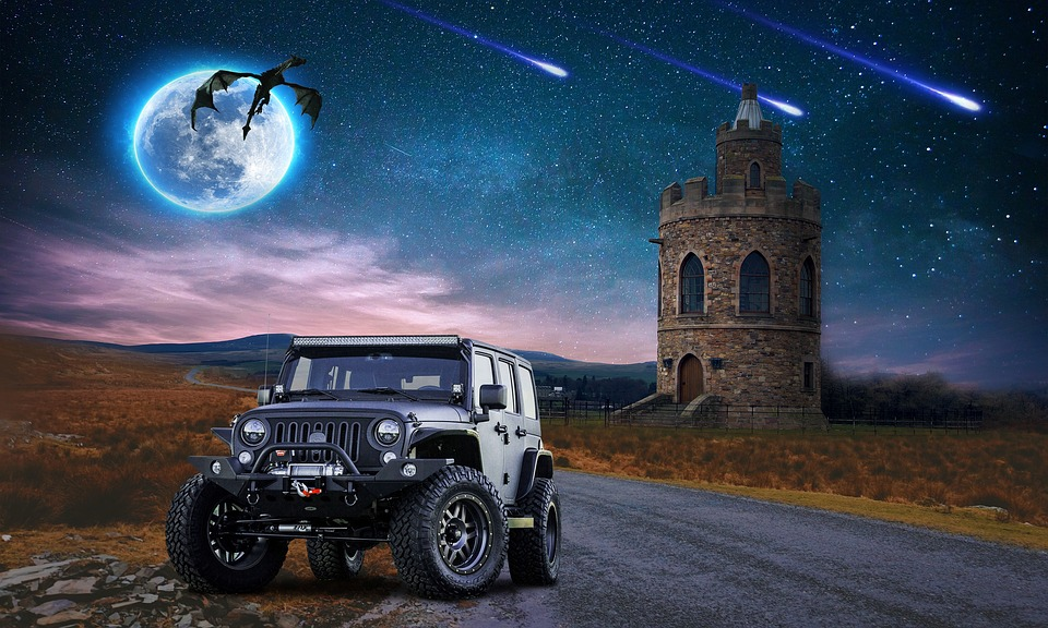 A nightscape with a modern jeep in the forefront next to a road.  The silhouette of a flying dragon and a castle are in the background.